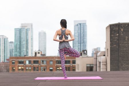 woman-standing-on-pink-yoga-mat-meditating-373946